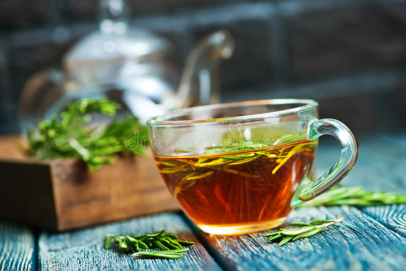 Rosemary tea. In cup and on a table royalty free stock image