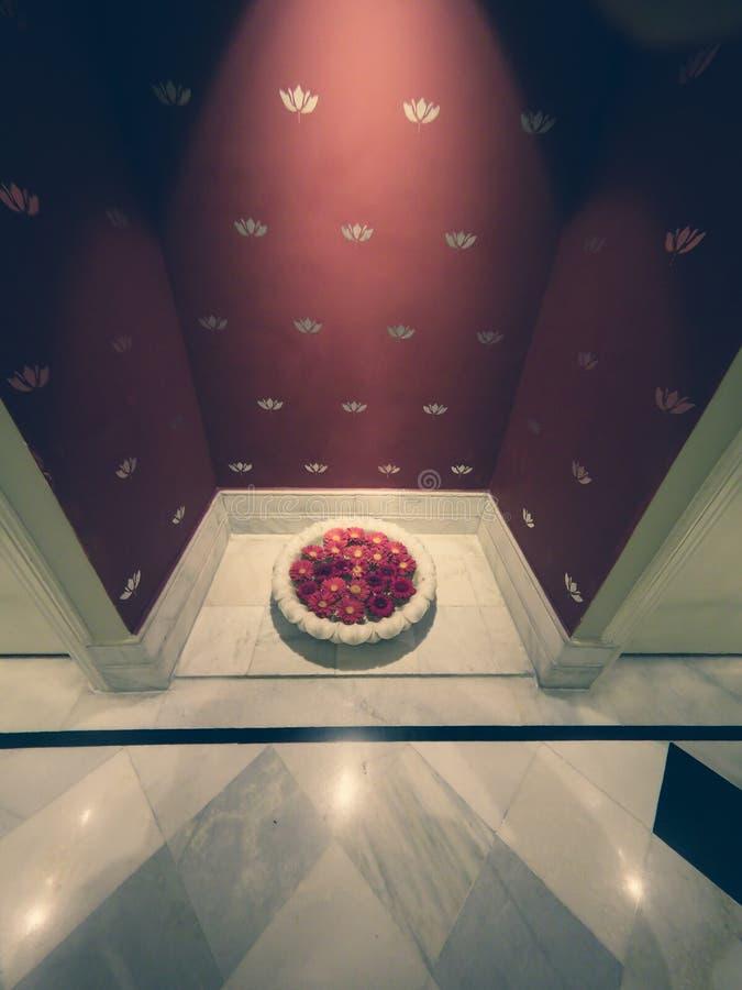 Rosen-Blumenblätter in einer Schüssel Wasser gelegt in eine Nische mit Marmorboden am Eingang zu einem Luxusbadekurort stockbilder
