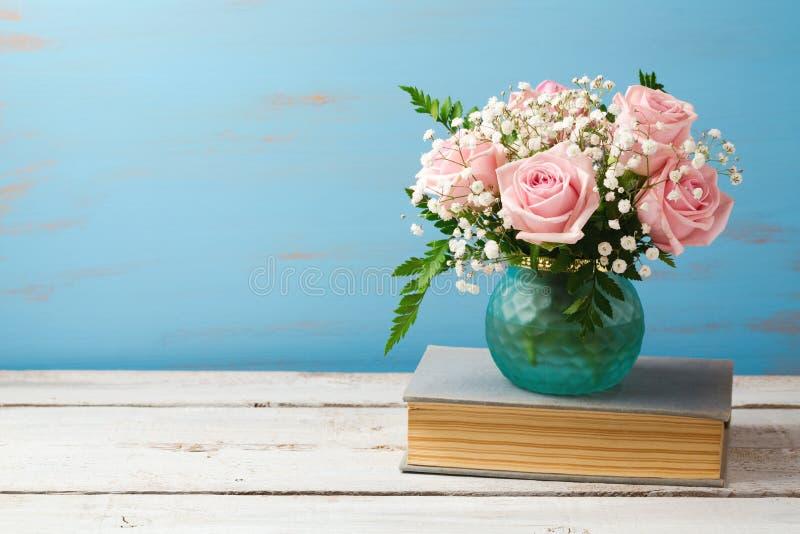 Rosen-Blumenblumenstrauß im Vase auf alten Büchern über hölzernem Hintergrund lizenzfreie stockfotos