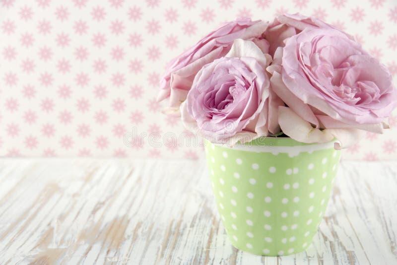 Rosen in einem grünen polkadot Vase auf Weinlese lizenzfreies stockfoto