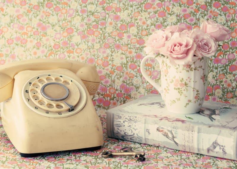 Rosen in einer Kaffeetasse und einem Telefon lizenzfreie stockbilder