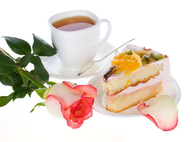 Rosen-Kuchen mit Früchten und Tasse Tee lizenzfreie stockbilder
