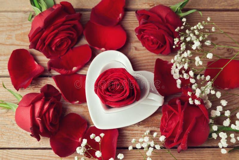 Rosen mit Herzen formen Kaffeetasse auf hölzernem Hintergrund Ansicht von oben lizenzfreie stockfotografie