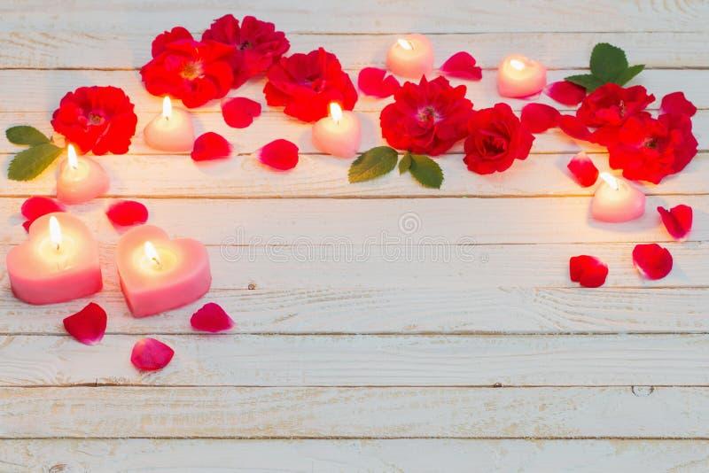 Rosen und brennende Kerzen auf hölzernem weißem Hintergrund stockfotos