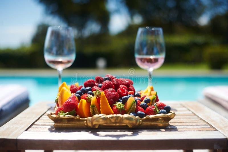 Rosen-Wein im Glaspool- und -fruchtsommer lizenzfreie stockfotos