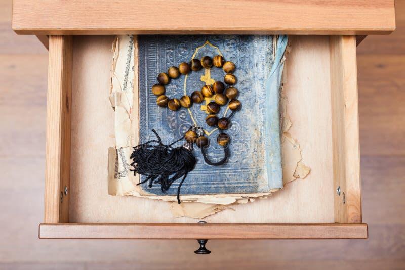 Rosenbeet auf altem religiösem Buch im offenen Fach stockfotografie