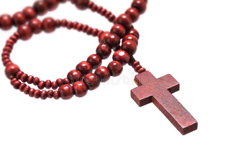 Rosenkranzperlen mit dem Kreuz gemacht vom roten Holz lokalisiert auf einem weißen BAC stockfotografie