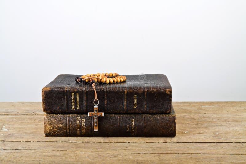 Rosenkranzperlen und Bücher der Liturgie der katholischen Kirche lizenzfreie stockfotografie