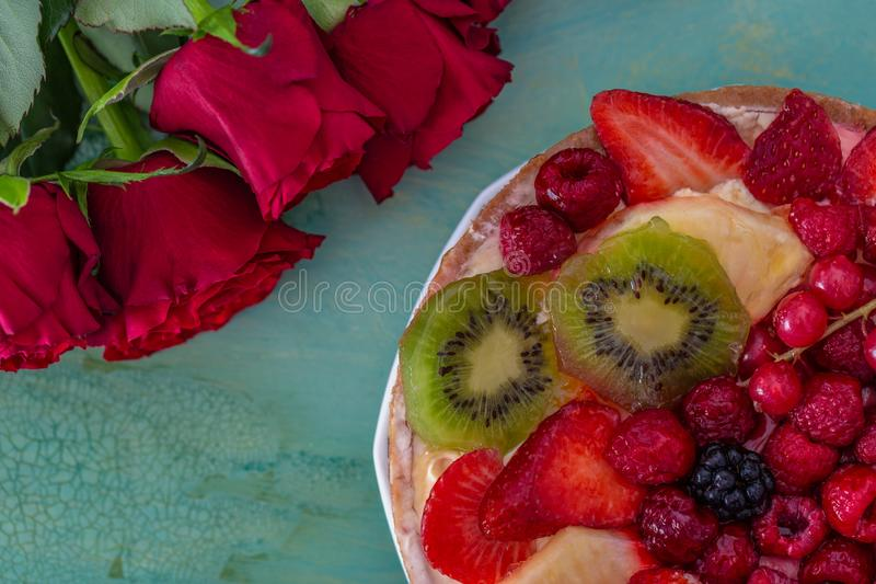 Roses and beautiful delicious sweet cake with berries on a green background. royalty free stock image