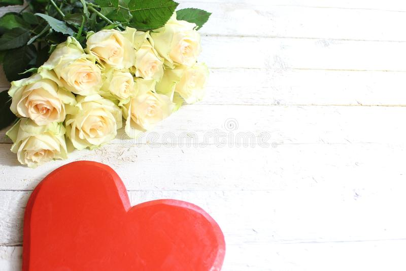 Roses blanches et un coeur rouge sur un fond en bois blanc images libres de droits