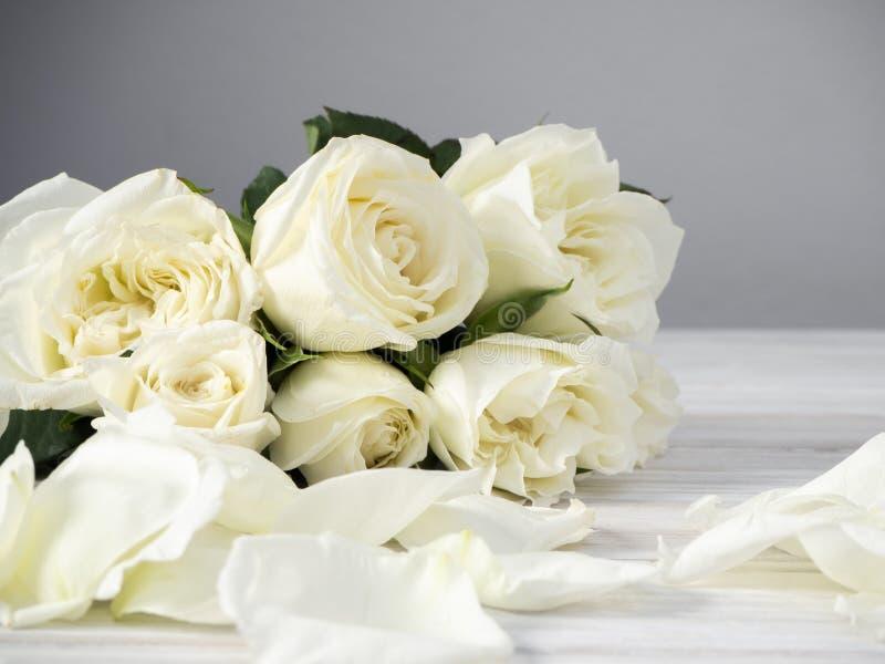Roses blanches sur une table en bois blanche image stock
