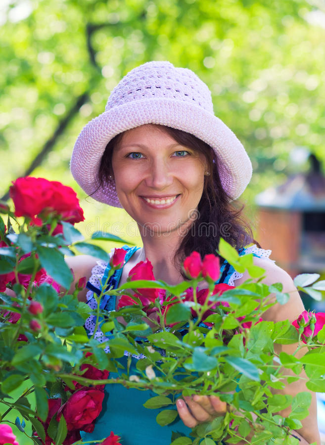 Roses bush. The woman in a hat with roses bush stock image