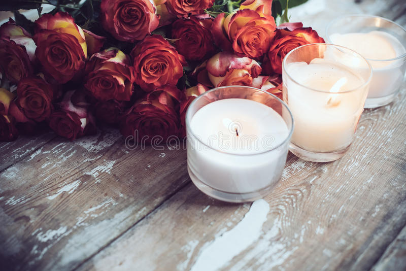 Roses and candles. Vintage holiday decor, a bouquet of red roses and burning candles on an old wooden board surface, wedding decoration royalty free stock photo