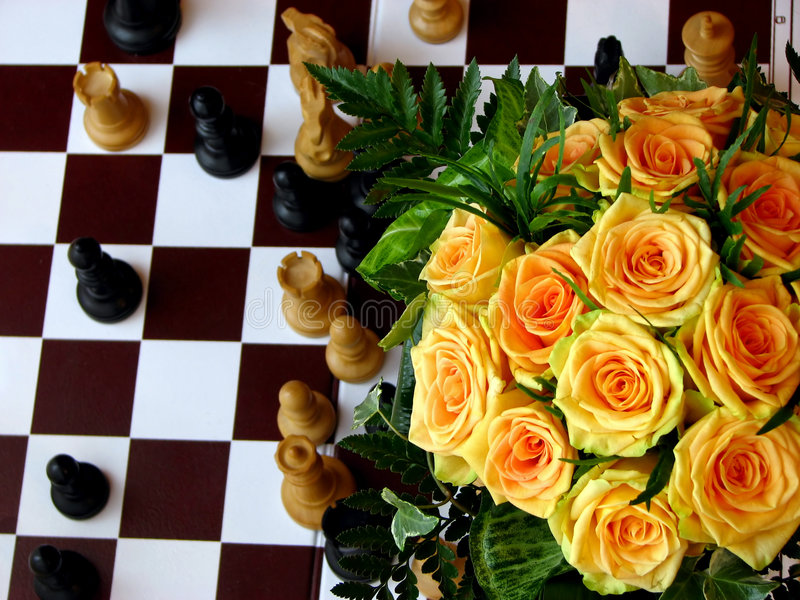 Roses on chess board royalty free stock image