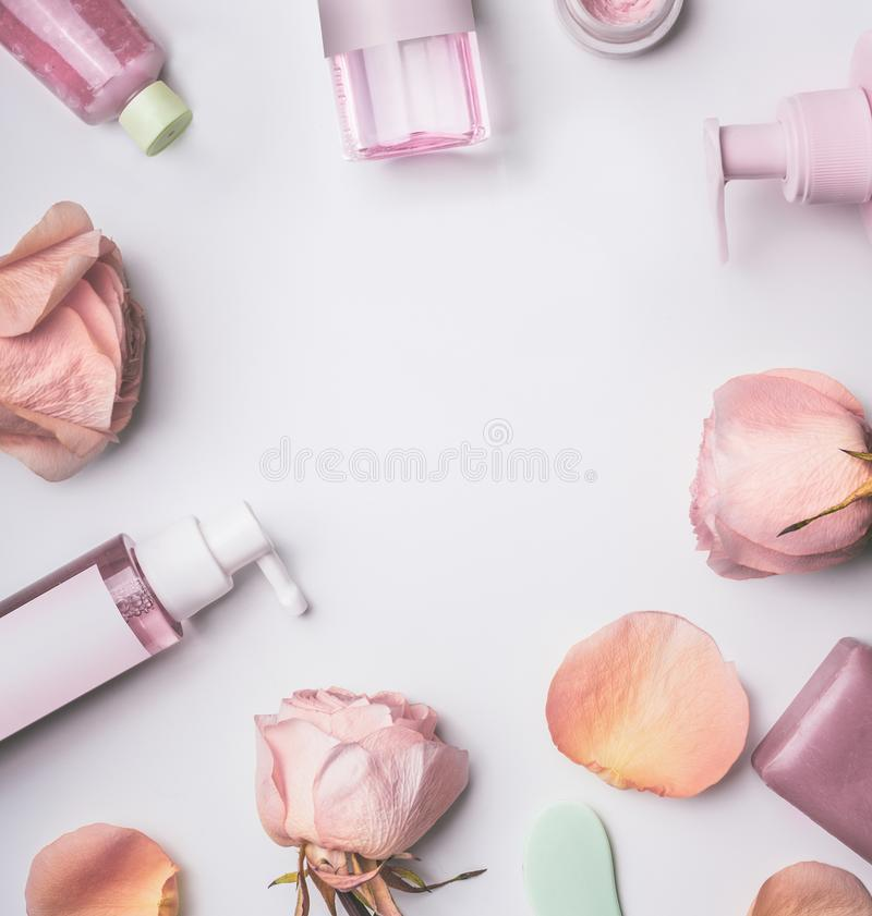 Roses cosmetics frame with toner,serum, essence,moisturizer and others on white desktop. Background, top view. Facial Skin care beauty treatment royalty free stock images