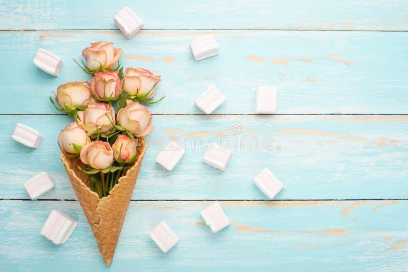 Roses roses dans un cône avec la crème glacée sur un fond en bois bleu, cadeau de concept pour le fond de fête aimé, anniversaire photos stock