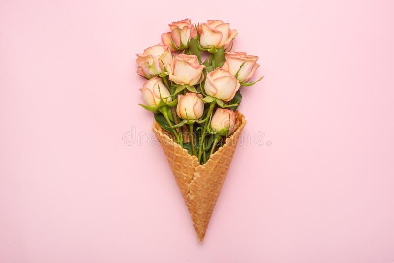 Roses roses dans un cône avec la crème glacée sur un fond rose, cadeau de concept pour votre fond de fête aimé, anniversaire, mar image stock