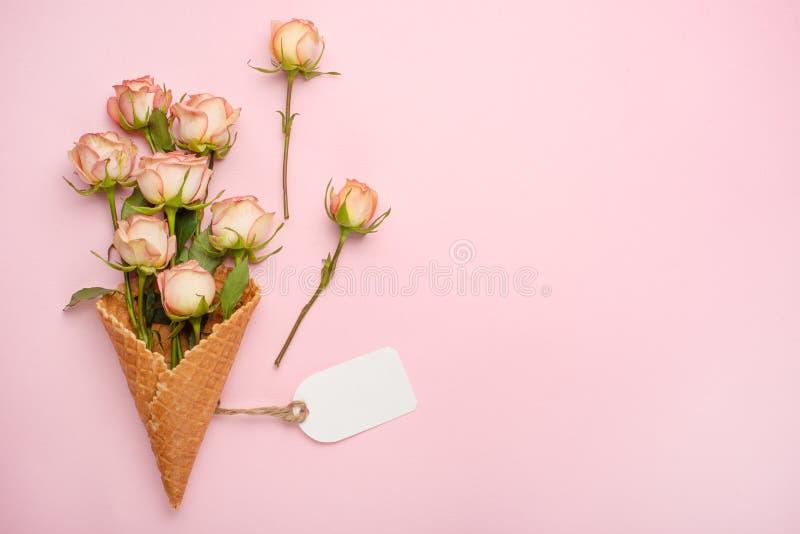 Roses roses dans un cône avec la crème glacée sur un fond rose, cadeau de concept pour votre fond de fête aimé, anniversaire, mar photos stock