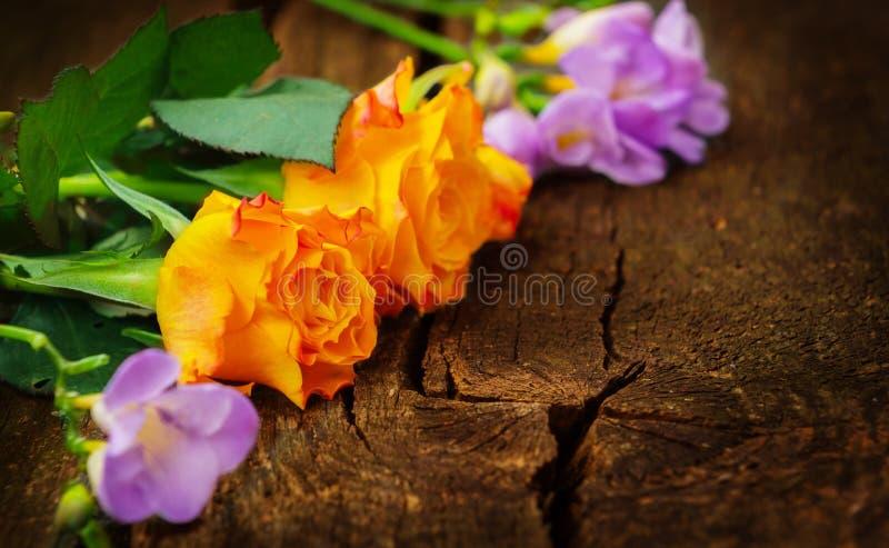 Roses et freesias sur le bois photos libres de droits