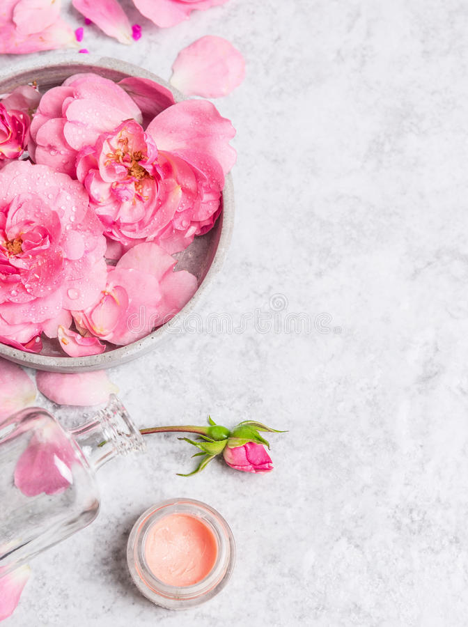Roses in gray bowl with water , cream and pink bottle with Booth. On stone background stock images