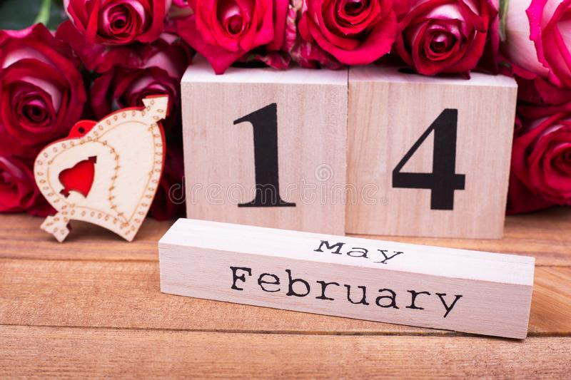 Roses, heart and wooden calendar. February 14 on calendar, roses and heart stock photo