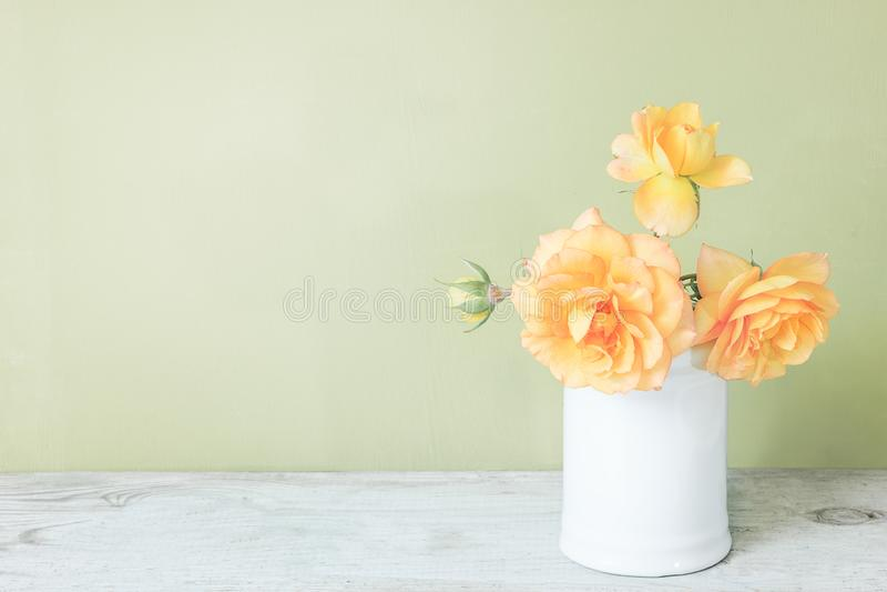 Roses jaunes dans le rétro vase blanc sur la table en bois sur le mur vert avec l'espace de copie image libre de droits