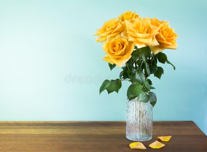 Roses jaunes dans un vase en verre sur la table en bois images stock