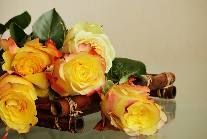 Roses sur un plateau en bambou photographie stock