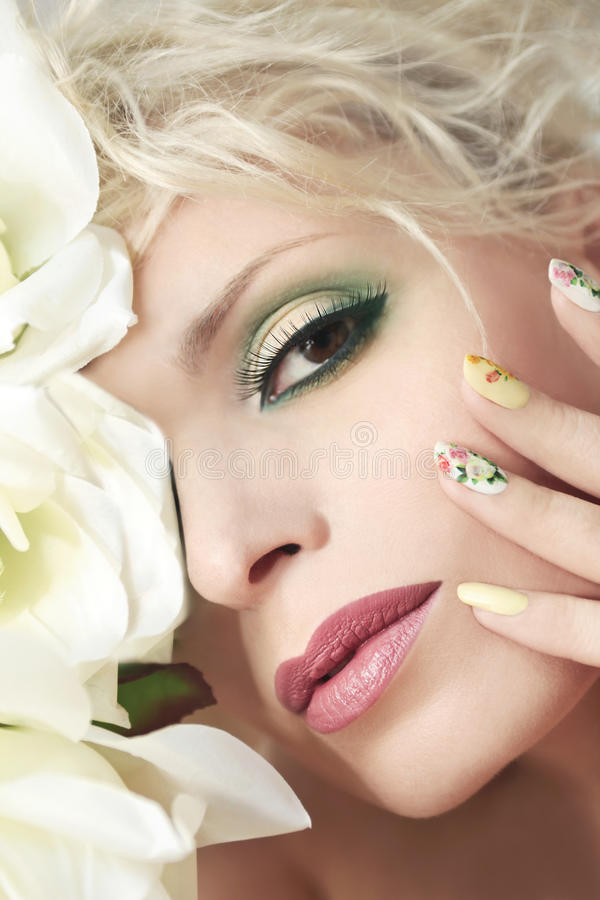 Roses. The makeup on the girl with roses on her head and a design on the nails stock images