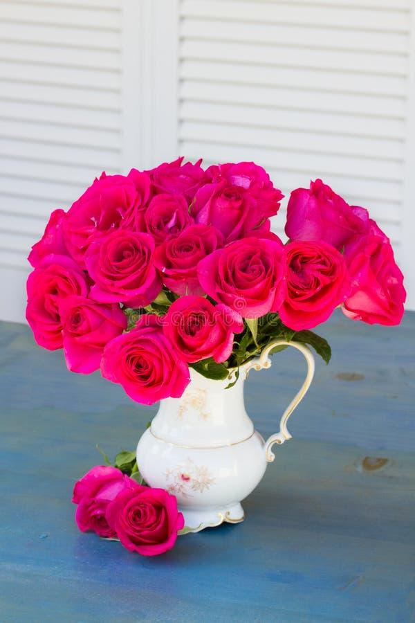 Roses mauve dans le vase sur la table bleue photographie stock libre de droits
