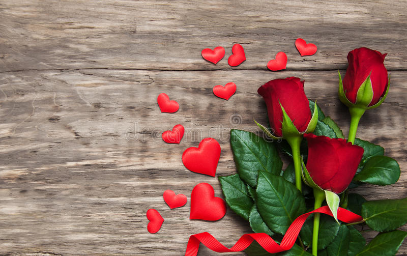 Roses and red hearts. On a white wooden background royalty free stock photos