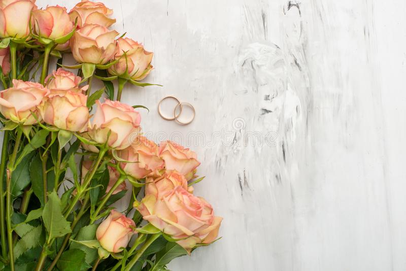 Roses with rings on a marble background, festive background, anniversary, wedding, Valentine`s Day.  stock photo