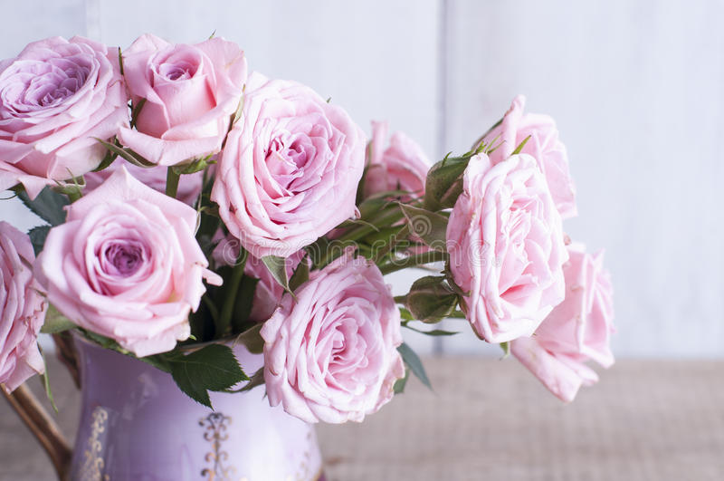 Roses roses dans une cruche de vintage photos stock