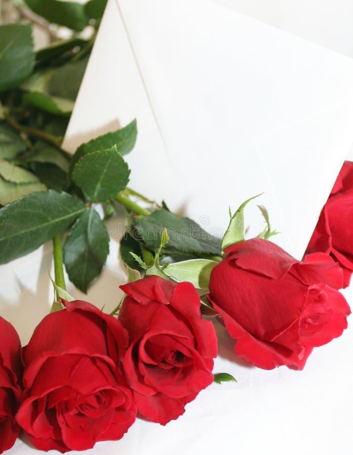 Roses rouges avec une note blanche photo stock