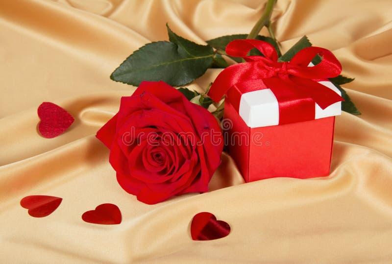 Roses rouges et boîte-cadeau sur le tissu d'or photographie stock