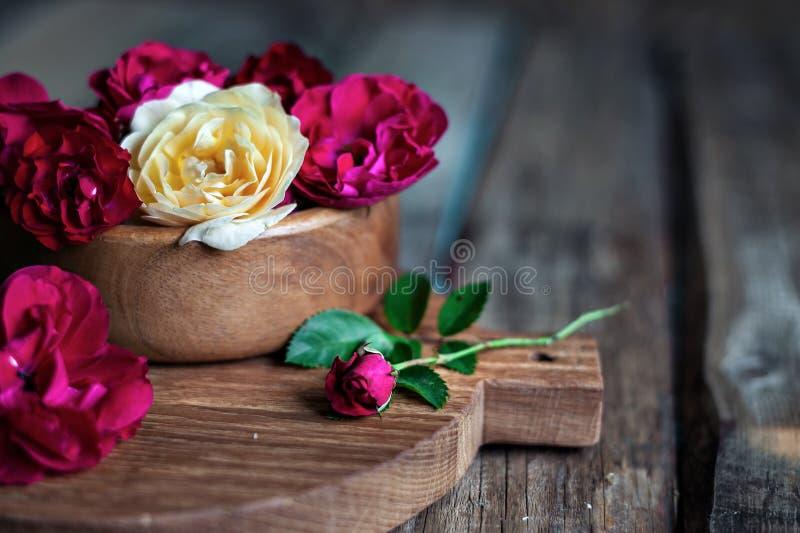 Roses rouges, roses et de thé dans une cuvette en bois sur le fond de vintage photographie stock