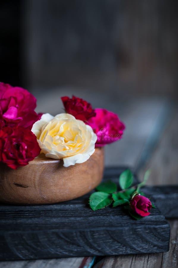 Roses rouges, roses et de thé dans une cuvette en bois sur le fond de vintage images stock