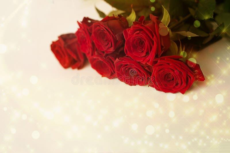 Roses rouges sur un fond clair avec les points culminants et le bokeh d'or photos stock