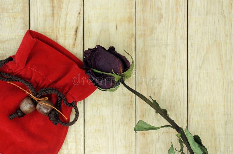 Roses sèches avec le petit sac rouge sur le fond en bois de modèle photographie stock libre de droits