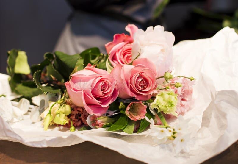 Roses sur la table du ` s de fleuriste, moments fonctionnants image stock