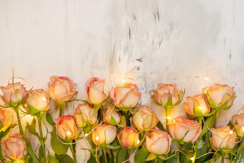 Roses roses sur un fond de marbre avec la guirlande atmosphérique, un cadeau de concept pour votre fond préféré de vacances, anni images stock