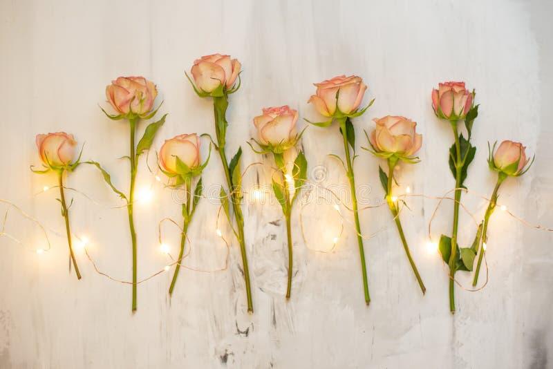 Roses roses sur un fond de marbre avec la guirlande atmosphérique, un cadeau de concept pour votre fond préféré de vacances, anni photographie stock