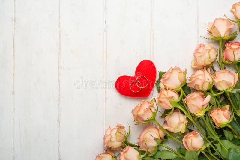 Roses roses sur un fond en bois blanc avec des coeurs, fond de fête, anniversaire, mariage, Saint-Valentin Configuration plate vu photographie stock