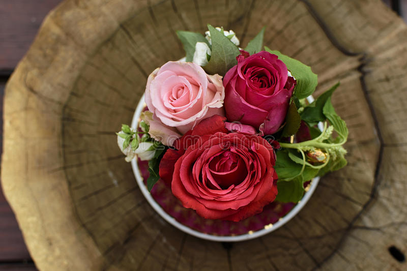 Roses. Three roses in a vase on a wooden stump stock photography