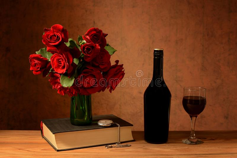 Roses in a vase, books and wine stock photos