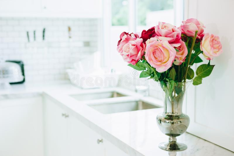 The roses. The vase is made of glass filled with colorful roses laying in front of the sink in the kitchen area stock photography