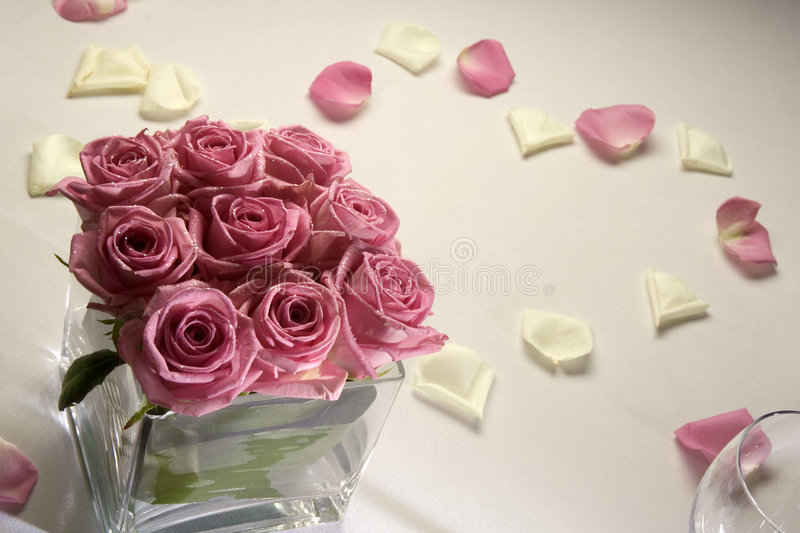 Roses on wedding table. With petals forming a heart
