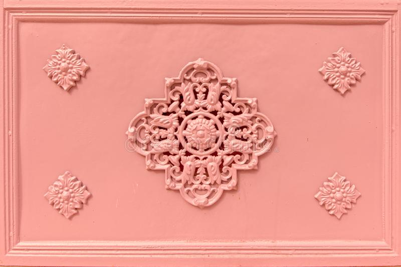 Rosette decoration on an old light pink iron cast door. Rosette decoration on a traditional portuguesed light pink painted iron cast door stock photos