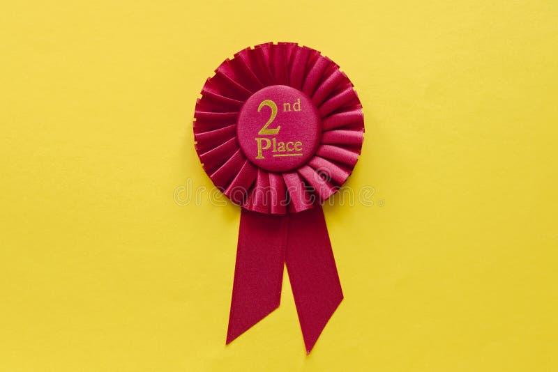 rosette rouge de ruban de gagnants de 2ème endroit sur le jaune photos libres de droits