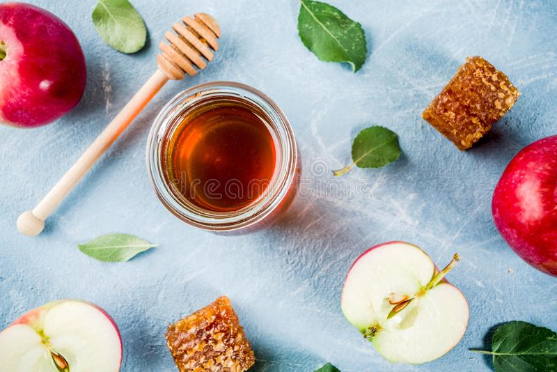 Rosh Hashanah concept. Jewish holiday Rosh Hashanah or apple feast day concept, with red apples, apple leaves and honey in jar, light blue background copy space stock images
